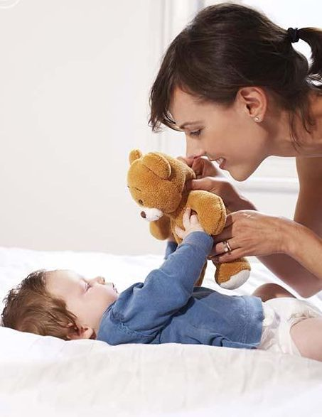 Mother and baby playing with teddy bear