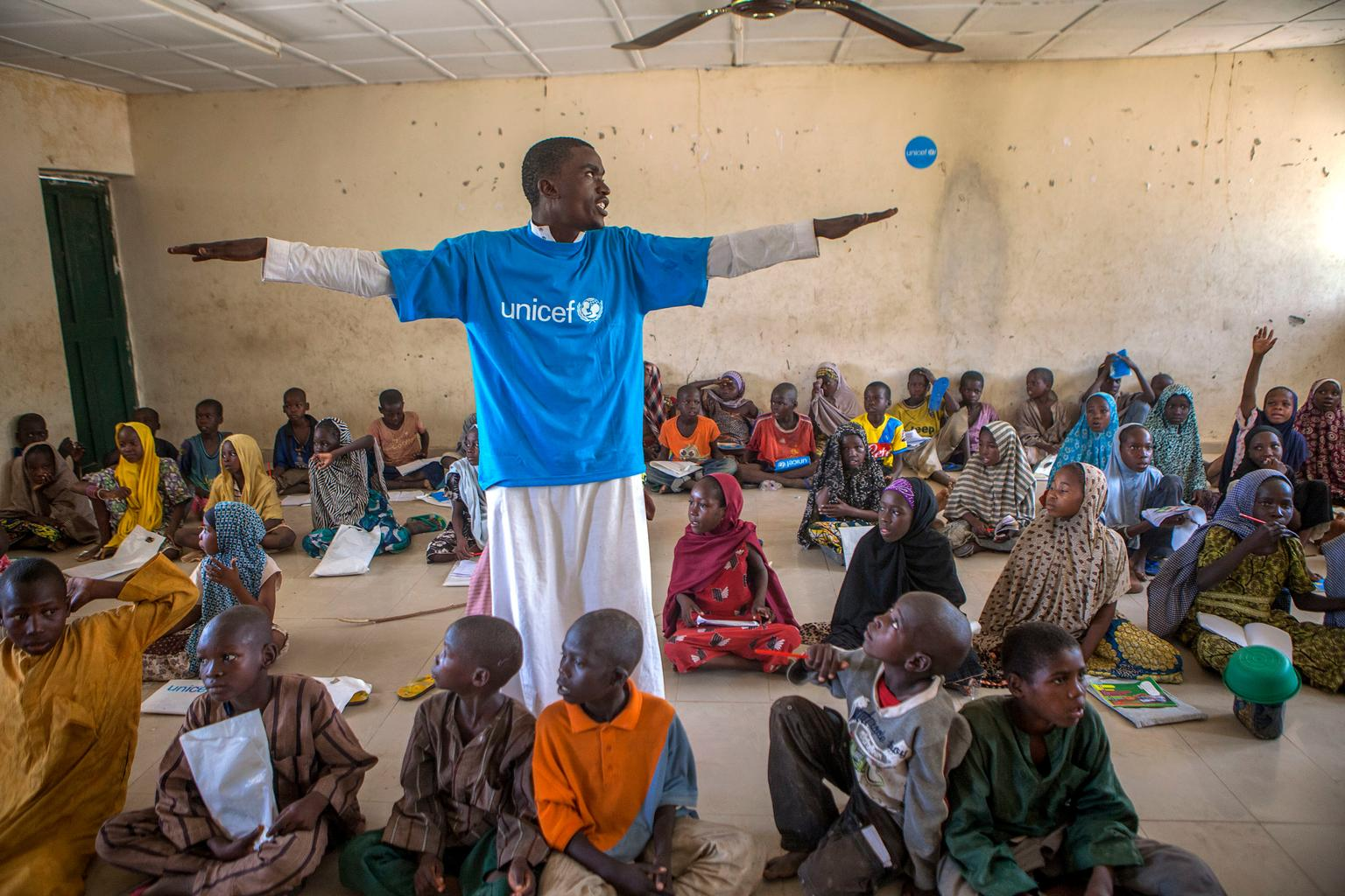 On 26 May, (standing), a teacher with his arms outstretched leads children in an activity at an informal learning centre in a UNICEF-supported safe space in the Dalori camp for internally displaced people, in the north-eastern city of Maiduguri in Borno State. He is wearing a T-shirt with the UNICEF logo, which is also on other items in the space.At end May 2015 in Nigeria, 15.5 million people, including 7.3 million children, are affected by the continuing crisis in the country's north-eastern region. More than 1.3 million Nigerians in the three states affected – Adamawa, Yobe and Borno – have fled their homes as a result of violence and attacks by Boko Haram insurgents that have escalated since the beginning of 2015. Many of the displaced, most of whom are children and women, are sheltering in host communities that have limited resources, and in formal and informal camps. All are in urgent need of basic supplies, health and nutrition services, and critical water, sanitation and hygiene (WASH) support to prevent the spread of disease. An estimated 200,000 people have also fled to neighbouring Cameroon, Chad and the Niger, further straining already vulnerable communities. The impact of the crisis on children and women is of particular concern. Many of them have lost their homes and belongings – escaping with only the clothing they were wearing; and some have walked for days – or even weeks – to find refuge. Many children in the region have been traumatized and are in need of psychosocial support. They have witnessed violence and atrocities, including seeing parents and siblings slaughtered by Boko Haram insurgents; and have been exposed to or have experienced violence and brutality. Their homes have been burned and their schools have been damaged or destroyed during the attacks. The insurgency has also created a larger humanitarian crisis in the region. UNICEF is working with the Government and other partners, including other United Nations organizati